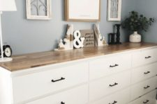 a large sideboard made of several Malm dressers with black handles and a single light-stained countertop