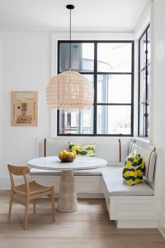 a light-filled dining area by the windows, with a built-in corner bench, a round table, a woven chair and a pendant lamp