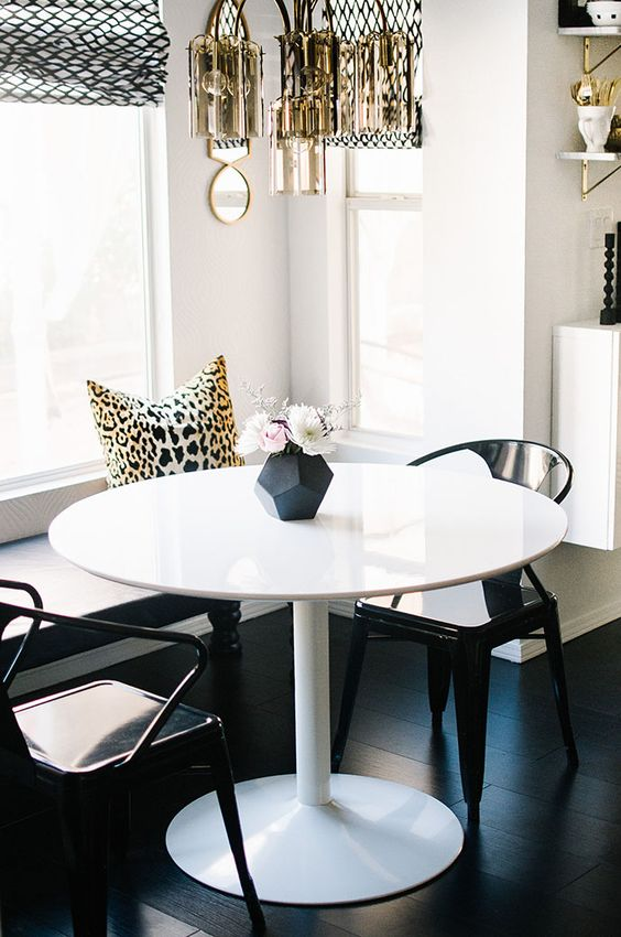a little glam dining space with a built-in bench, a round table, black chairs, a gilded chandelier, printed elements