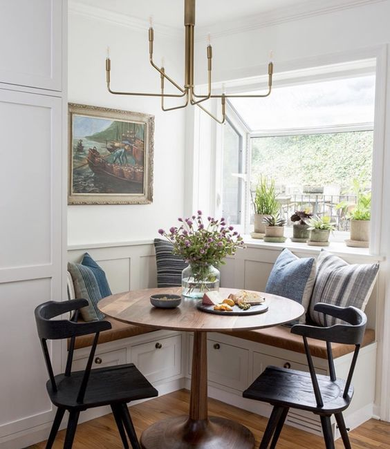 a lovely farmhouse dining nook with a built-in corner bench, printed pillows, a round table, black chairs and a gidled chandelier