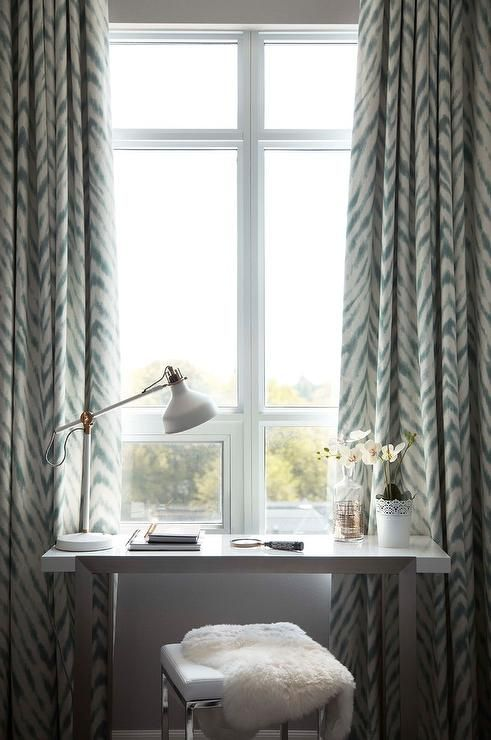 a lovely makeup space by the window, with a tiny vanity, a stool and a white IKEA Ranarp table lamp