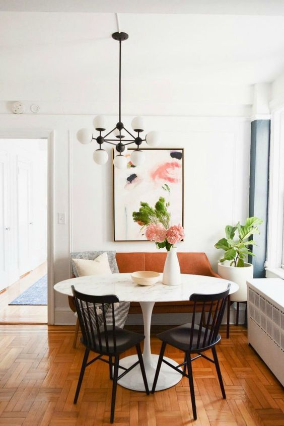 a lovely modern dining area with a rust-colored leather loveseat, printed textiles, a round table, black chairs, a modern chandelier