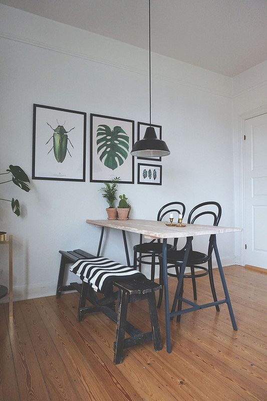 a lovely modern dining nook with a light stained table, a black bench and chairs, a small gallery wall with cool prints