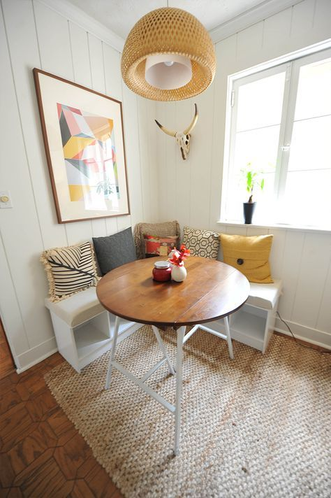 a lovely small dining nook with a corner storage bench, colorful pillows, a round table, a bold artwork and a woven pendant lamp