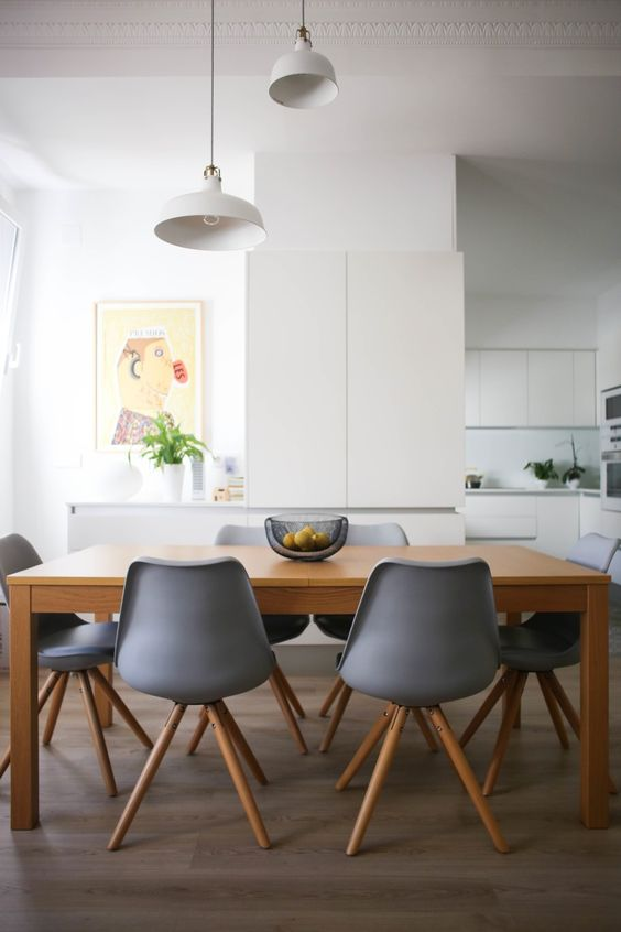 a minimalist dining space with a wooden table, grey chairs, white IKEA Ranarp pendant lamps is very cozy