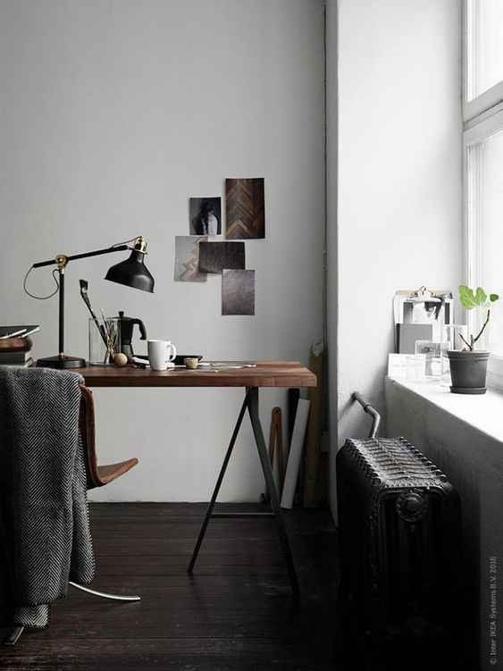 a moody home office nook with a trestle desk, a leather chair, a black radiator and a black IKEA Ranarp table lamp