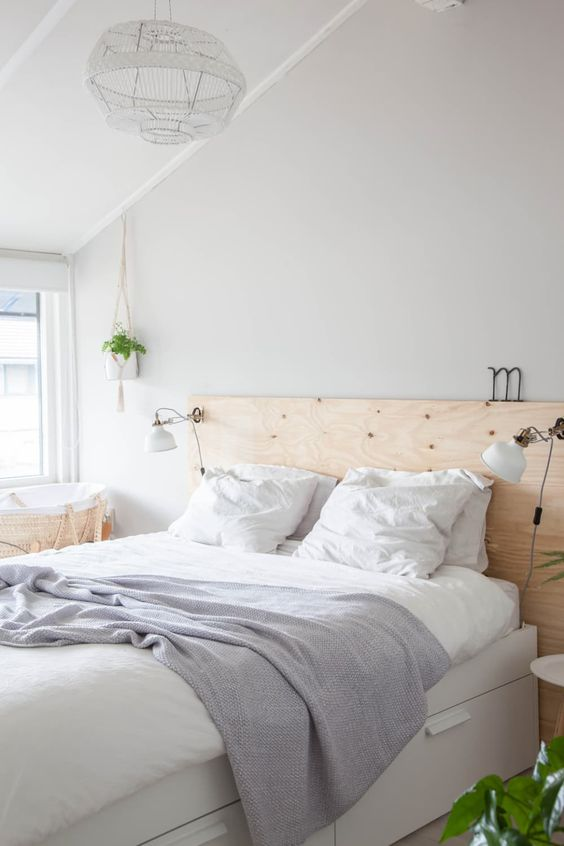 a neutral Nordic bedroom with a white bed with storage, a plywood headboard, IKEA Ranarp sconces that brign light