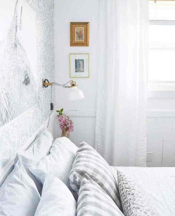 a neutral and peaceful bedroom with an accent wallpaper wall, a bed, printed bedding and IKEA Ranarp sconces