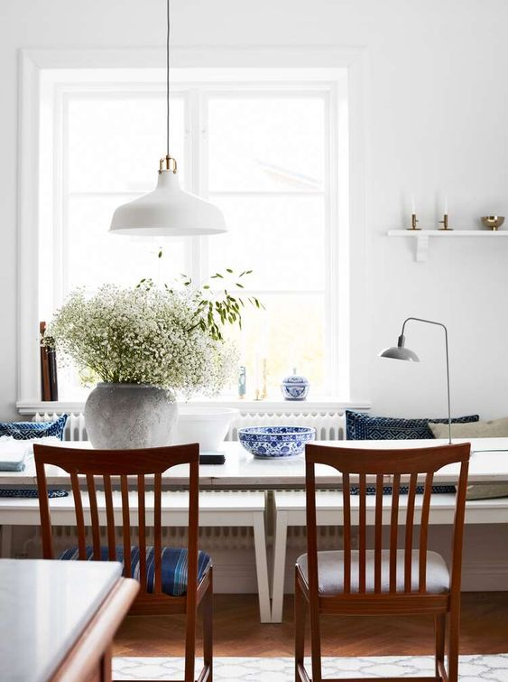 a peaceful dining space with simple and elegant furniture, greenery, chic porcelain and a white pendant IKEA Ranarp lamp