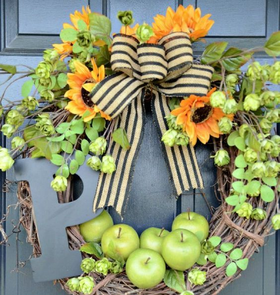a rustic fall wreath of vine, foliage, greenery, bright blooms, apples, a striped bow and a large monogram