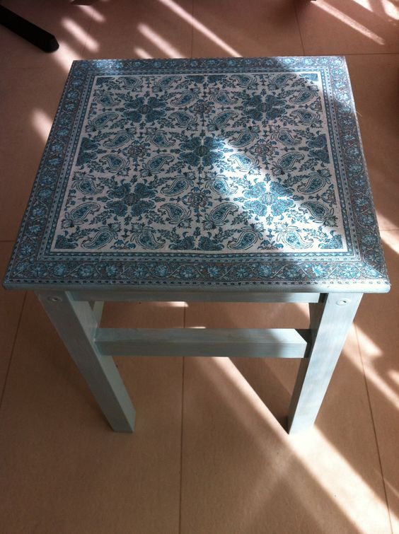 a slate blue IKEA Oddvar stool with a beautiful decoupage seat can be used as a side table or a chair