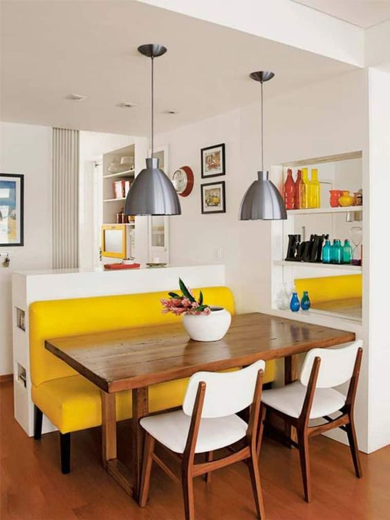 a small and bright dining space with a yellow upholstered bench, a stained table, white chairs, metal pendant lamps