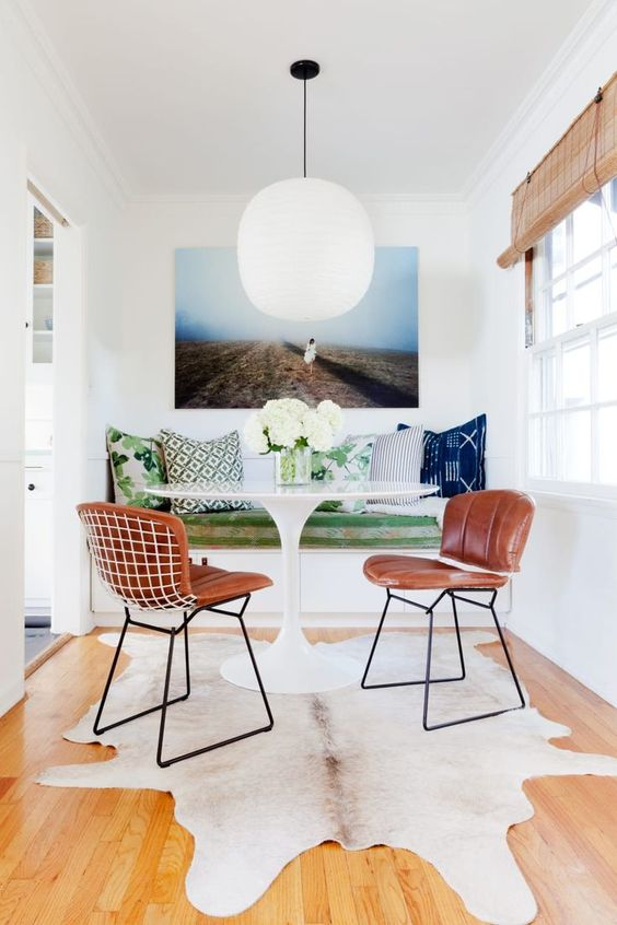 a small and colorful dining area with a built-in bench, a round table, leather chairs, a rug and a bold artwork