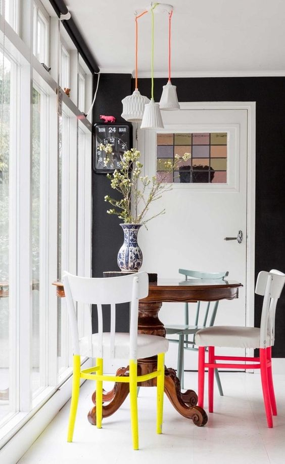 a small and colorful dining space with a vintage dark stained round table, chairs with colorful legs, pendant lamps on colorful cords