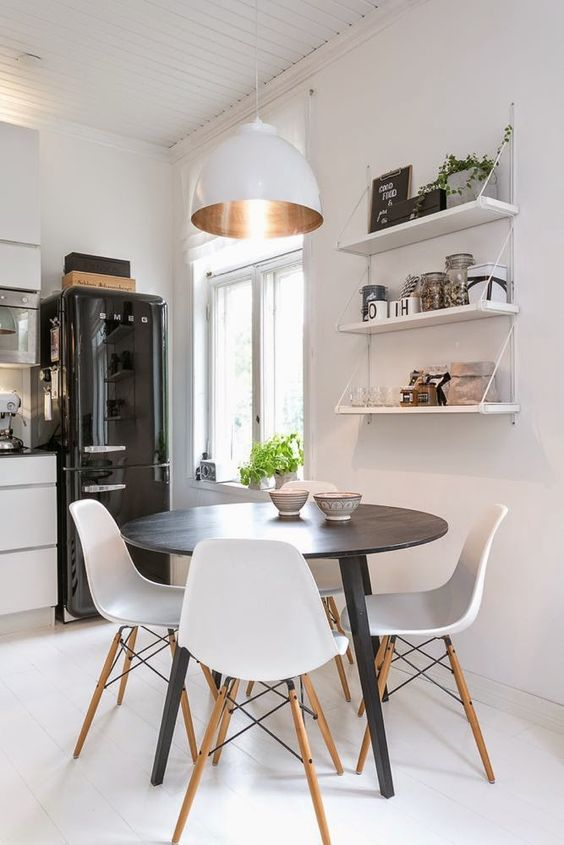 a small and cozy dining nook with open shelves, a round table, white chairs, a chic white pendant lamp