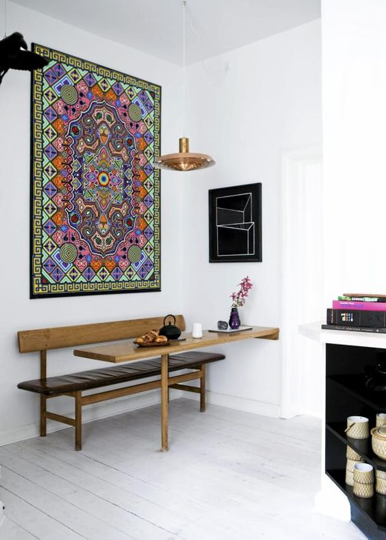 a small and lovely boho dining nook with a colorful printed rug, a sleek leather bench and a built-in table, a pendant lamp and a cool vase