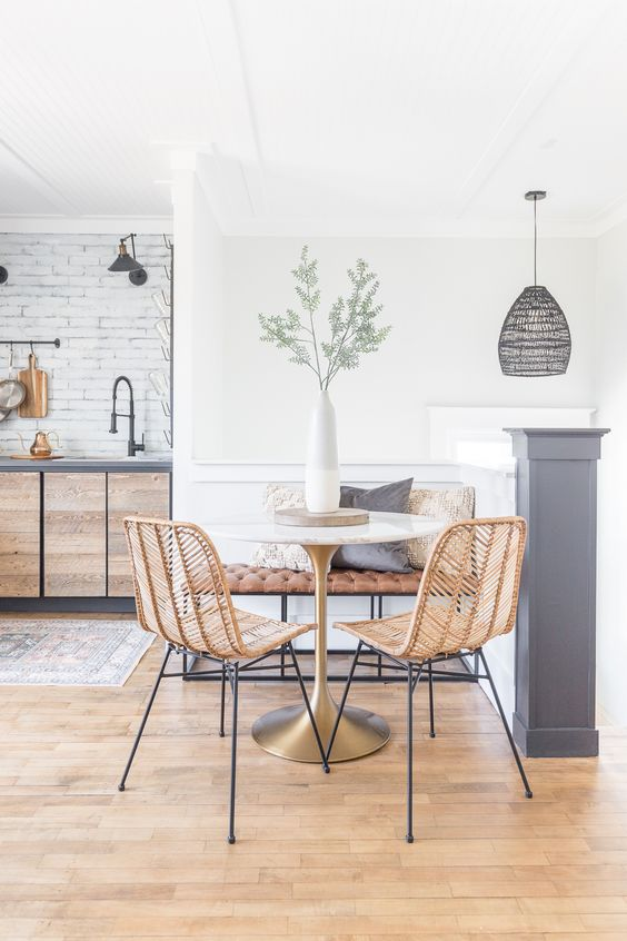 a small and stylish farmhouse dining nook with a leather bench, a round table, rattan chairs, a vase with greenery