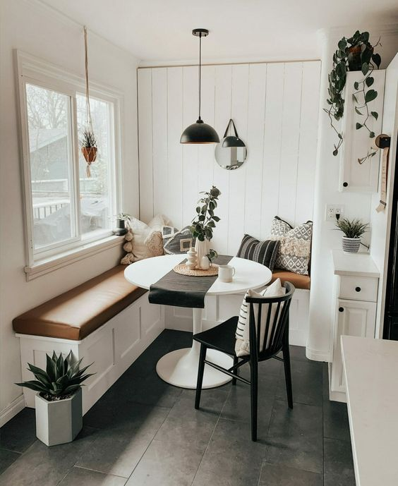 a small boho dining space with a built-in corner bench with a leather cushion, a round table, a black chair, a pendant lamp