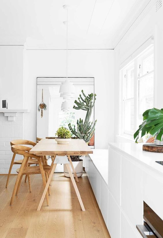 a small modern dining area filled with light, with a built-in bench, a trestle table, light stained chairs and some potted plants