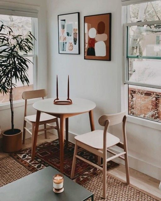 a small modern dining nook with a round table, wooden chairs, a pretty gallery wall, a potted plant and layered rugs