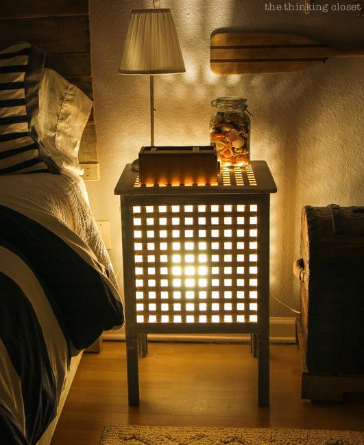 a small nightstand with a lamp inside is a romantic night light that will create a mood in the space