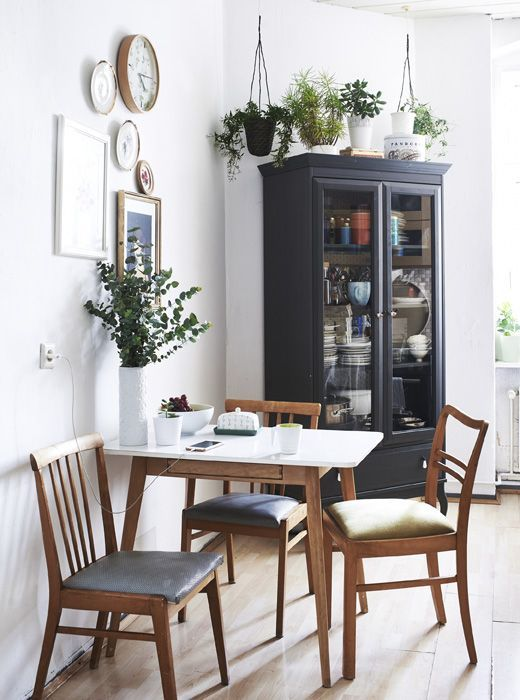 a stylish modern dining nook with a table, blue and green chairs, greenery in pots and vases and a gallery wall with clocks and plates