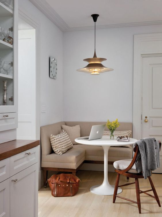 a stylish small dining nook with a tan corner bench, a round table, a white chair, a chic pendant lamp, printed pillows