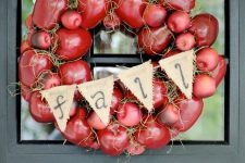 a super bold fall wreath of faux red apples, hay, a burlap banner and a plaid ribbon is cool for decorating your front door