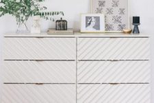 a trendy Tarva dresser hack with striped wall panels, light-colored stained legs and a frame and brass pulls
