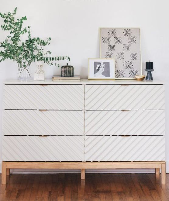 a trendy Tarva dresser hack with striped wall panels, light colored stained legs and a frame and brass pulls