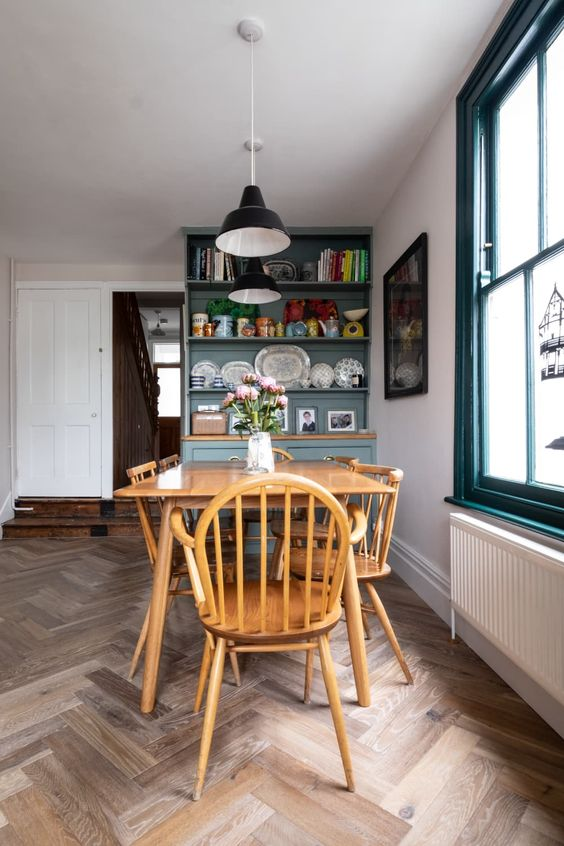 a vintage dining space with a wooden dining set, a blue storage unit and black pendant IKEA Ranarp lamps