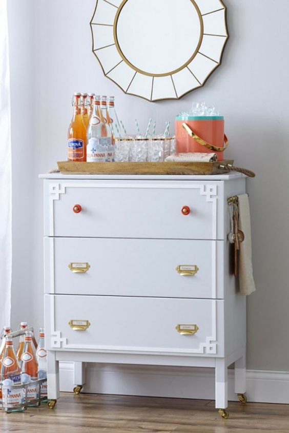 a whimsy IKEa Tarva hack in dove grey, with brass and red knobs plus white inlays and casters makes up a cool home bar