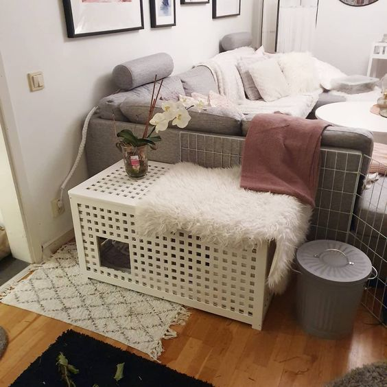 a white IKEA Hol side table with a pet retreat inside and a faux fur cover is a double-function item