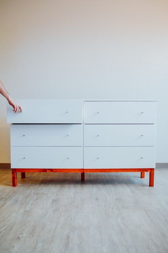 a white Tarva dresser hack with tiny knobs and a red frame and legs for a contemporary space