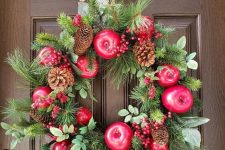 a wild fall wreath of evergreens, faux apples, pinecones, berries and eucalyptus plus a polka dot ribbon bow on top
