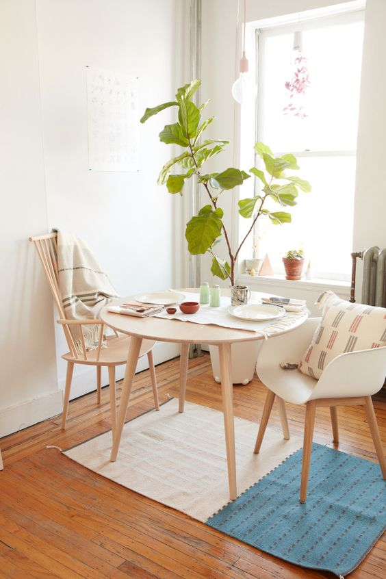 an airy small dining zone with a round table, stained and white chairs, potted plant, a hanging bulb and some printed textiles