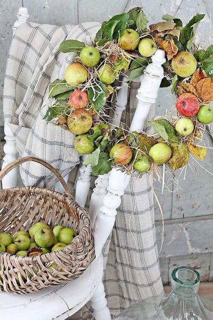 an all-natural fall wreath of real apples, foliage, hay is very rustic and farm-like, with partly dried leaves