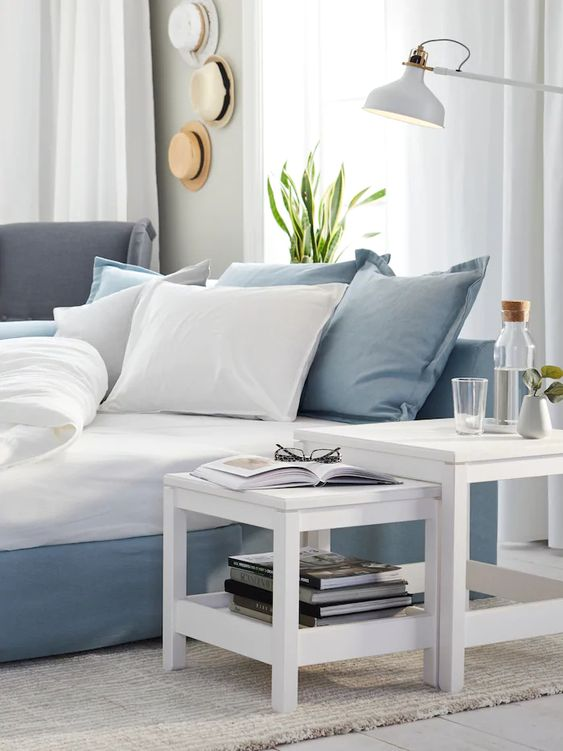 an ethereal blue and white coastal bedroom with a hat display, IKEA Ranarp floor lamp and mini white tables