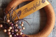 a Thanksgiving wreath covered with rust yarn, with fabric flowers, berries and feathers and a wide ribbon