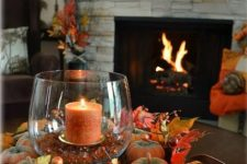 a basket tray with faux pumpkins, berries, leaves and a rust-colored candle in a candle holder with rust rhinestones is very rustic and cool