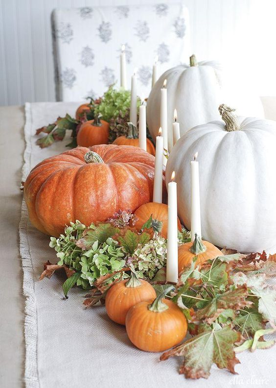a beautiful and natural fall centerpiece of green blooms, fall leaves, gourds and pumpkins and thin and tall candles
