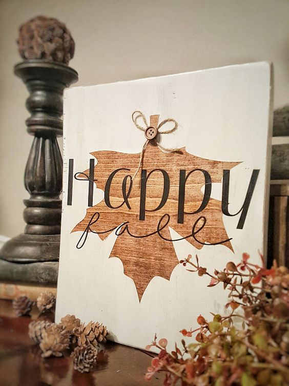a beautiful fall sign in white and with a stained fall leaf and a button is super cute and fun