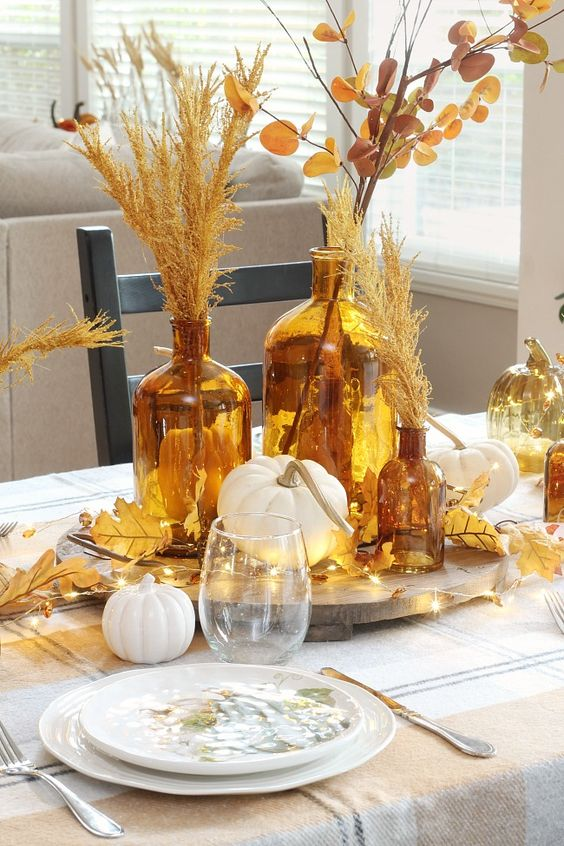 a beautiful rust and gold centerpiece of pumpkins, apothecary bottles with grasses and leaves and lights