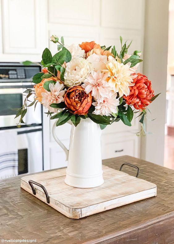 a bold and fun fall faux flower arrangement of neutral, blush and red blooms and greenery is very elegant