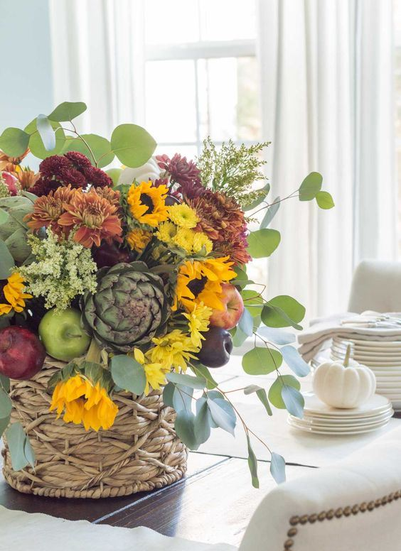 a bold fall centerpiece of yellow, orange and rust and burgundy blooms, greenery, faux apples and pears plus foliage