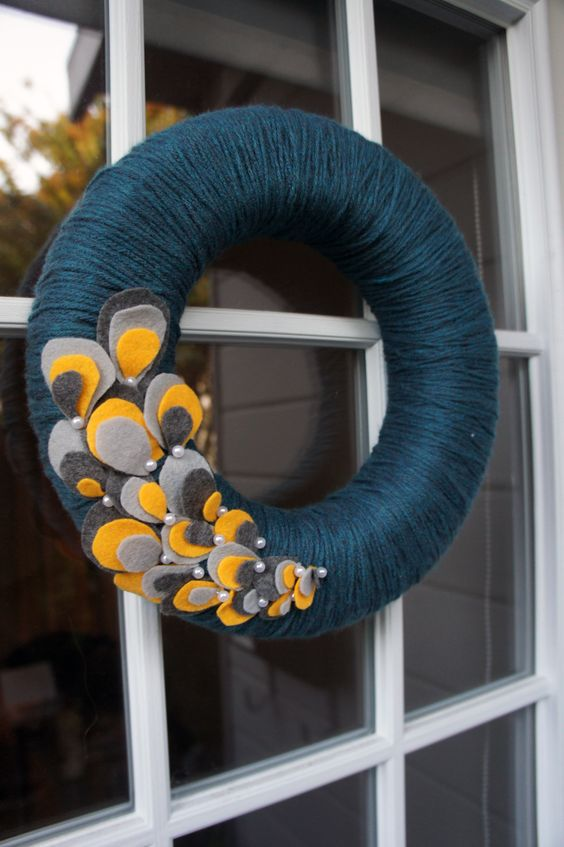 a bold fall wreath styled in non-typical colors, covered with navy yarn and with colroful fabric petals and pearls
