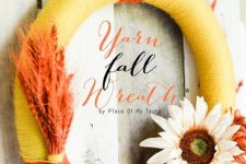 a bold yarn fall wreath covered with orange and yellow yarn, with dried blooms and orange wheat
