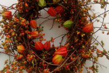 a branch and twig fal wreath with dried blooms, blooming branches and berries is a colorful fall piece