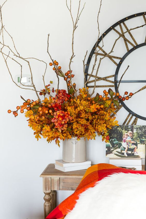 a bright and fun fall centerpiece of orange leaves, red blooms, branches with berries is a stylish idea