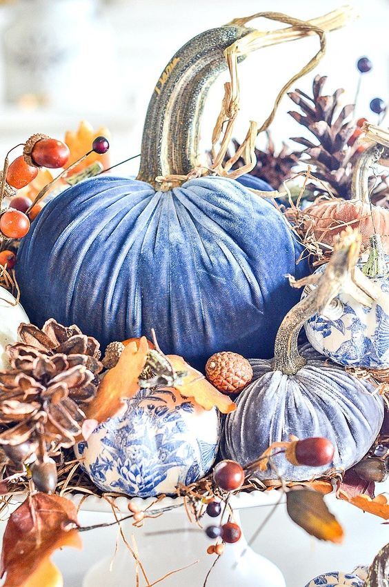 a bright fall centerpiece of blue velvet pumpkins, white and blue usual ones, pinecones and berries, acorns and husks